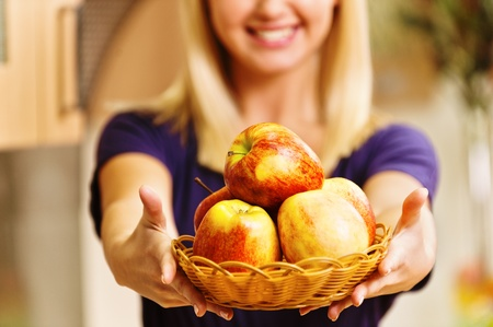 a beautiful young woman stretched out ahead basket with apples background of kitchen Stock Photo - 11480627