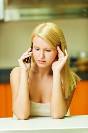 talks: portrait of young serious woman sitting at a desk talking on the phone looking down