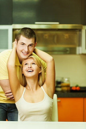 beautiful young woman sitting on a chair hugging a young man standing next background of kitchen photo