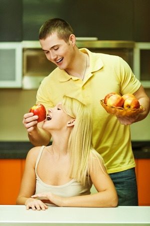 A young man gives a woman a blonde bite delicious, juicy apple background of kitchen photo