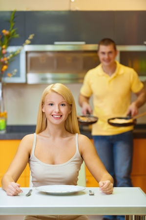 sprightly: young man prepared for breakfast and treats his favorite girl, pleasing her with his skill Stock Photo