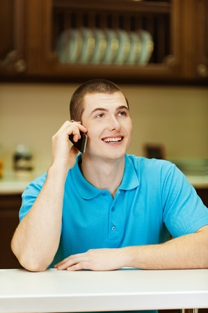 conversaciones: Sonriente joven hablando por teléfono celular mientras se está sentado a la mesa de la cocina con los platos contra el gabinete