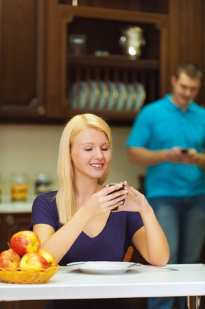 guy with a mobile phone in hands of blond girl looks at drinking coffee at kitchen table on which stood a vase on it with apples photo