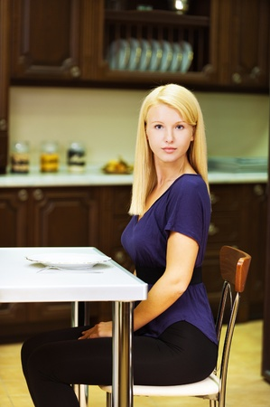 tunic: blonde girl in blue shirt and black pants while sitting at table posing against backdrop of kitchen furniture