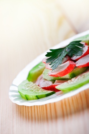 shred: Close-up summer salad with cucumbers and radishes, parsley, dressed in beautiful white saucer on wooden kitchen table