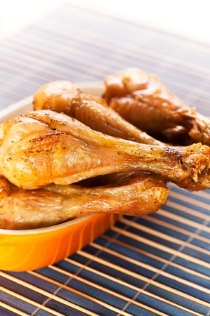four fried chicken drumsticks tasty dish in yellow on black bamboo napkin Stock Photo - 11480590