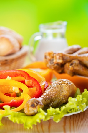 Lunch on green background: dish of fried chicken drumsticks delicious on lettuce leaves with sliced ​​circles of Bulgarian pepper in background transparent glass jug with milk and wicker vase with bread photo
