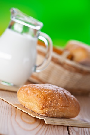 pone: on wooden table pone bun, pitcher of milk,on green background