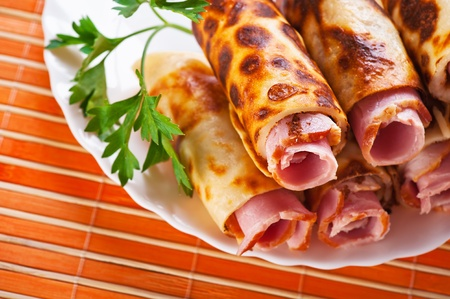 on white plate, close-up rolls with ham (bacon, sausage) is decorated with parsley against background of bamboo table photo