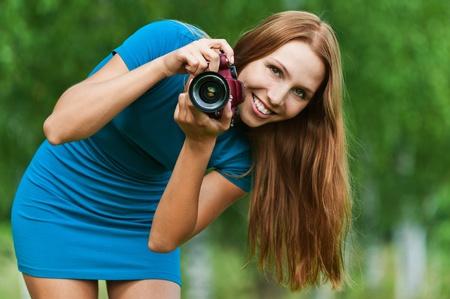 grappig, charmant, langharige vrouw leunt over met camera in de hand achtergrond zomer groen park Stockfoto