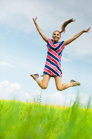 young, attractive woman in striped dress jumps up against the blue sky with clouds and green fields photo