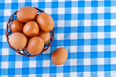 against the background of the table with checkered tablecloth, brown eggs in wicker basket photo