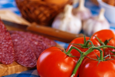 many snacks on the table on cutting board cut sausage (salami), garlic, tomato twig, wicker basket with eggs photo