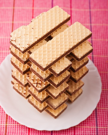 delicious waffles on plates lined up in tower on background of pink tablecloths Stock Photo - 11480520