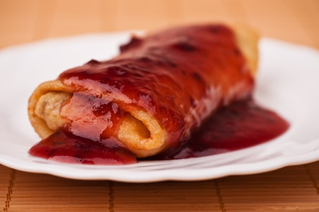 on white plate pancake stuffed with folded in roll filled jam against a bamboo napkin Stock Photo - 11480566