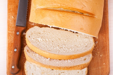 Close-up sliced bread (long loaf) on cutting wooden board, knife Stock Photo - 11480523