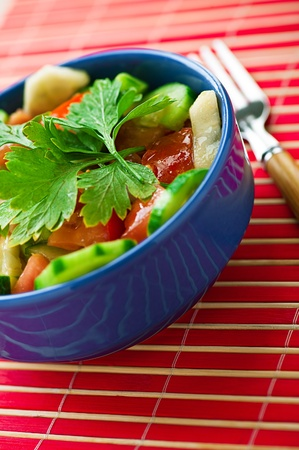 vegetable, vegetarian salad (cucumbers, tomatoes, parsley) in deep blue plate on the pink, bamboo towels Stock Photo - 11480517