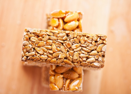 closeup two kozinaki with nuts (sunflower seeds, peanuts) against the background of the wooden kitchen table Stock Photo - 11480482