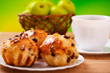 three plump cake with raisins, cup of coffee, tea, wicker basket with apples on green background photo
