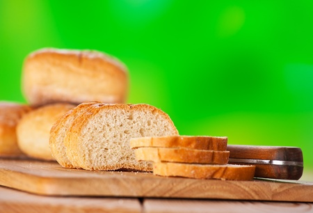 on cutting board wooden muffins, whole and sliced against the green background photo