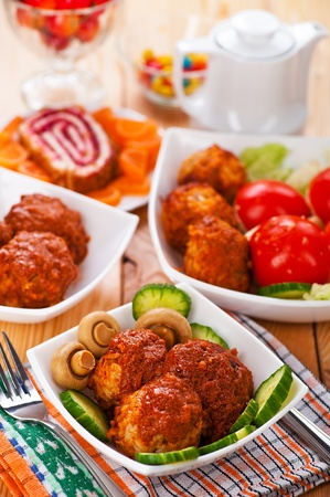 delicious lunch on wooden kitchen table in white bowl: meatballs, cucumbers, tomatoes, mushrooms, dessert (sweet roll, fruit, sweets) Stock Photo - 11480489