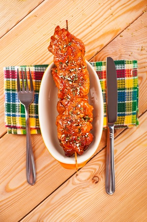 mouthwatering: against the background of the wooden kitchen table on checkered cloth, mouth-watering meat kebab (pork, beef, lamb, chicken) on skewer in large bowl, knife, fork Stock Photo