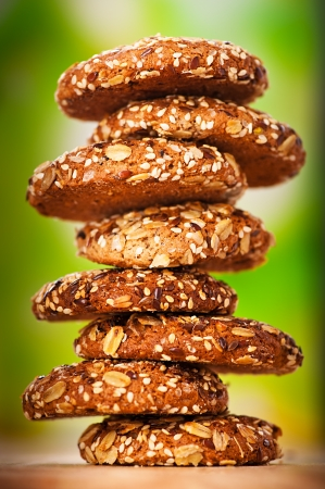 galletas integrales: deliciosas galletas de avena con el chapoteo de las semillas de girasol, semillas de s�samo en la mesa de madera dispuestos en fila sobre fondo verde