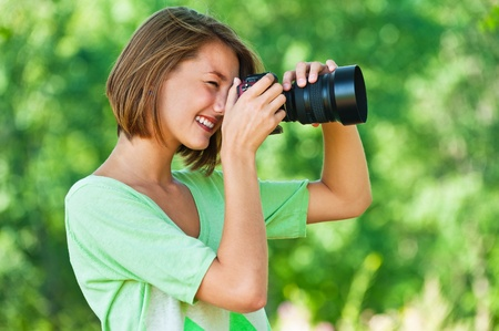 snapshot: portrait of charming, young, beautiful, short-haired woman in profile, photographs, against background of summer, green, nature
