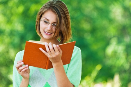 lovely, young woman standing in summer, green park reading book with glasses, smiling photo