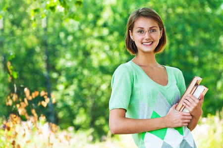bible reading: Portrait of pretty, slender student in glasses holding book against background of summer green park