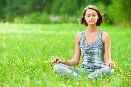 jonge, aantrekkelijke vrouw zit op groen gras (weide, glade) met gekruiste benen in de lotushouding te mediteren