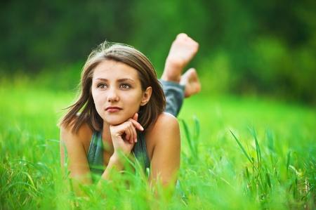 печальный: Портрет романтичной, молодой женщины с короткими волосами лежала на зеленой траве (луг, луг) босиком, мечты