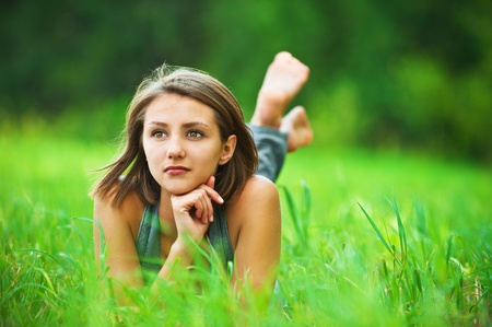 portrait of romantic, young woman with short hair lying on green grass (meadow, prairie) barefoot, dreams Stock Photo