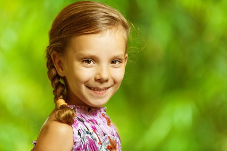 portrait of beautiful smiling girl with pigtail to green park background photo