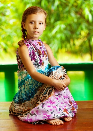 portrait of young, cute girl sitting on wooden table in long dress hugging his legs, against background of summer green park photo