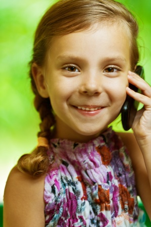 closeup portrait of young, cute girl with pigtail, said by mobile phone, smiling, on green background photo