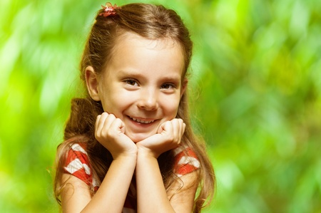 sprightly: closeup portrait of charming little, smiling girls leaning on arm chin on green background Stock Photo