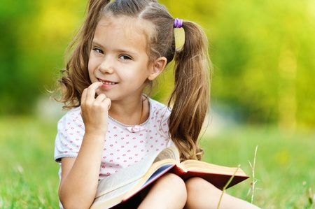 portrait of cute little girl with two tails was sitting on grass reading book on background of summer green park photo