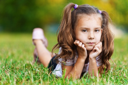 against background of green grass (meadows) is sad cute girl (child) with two tails leaning on palm photo