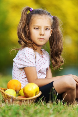 pretty sad portrait of child ( girl), sitting on green grass (meadow) with wicker basket with fruits (apples, oranges) photo