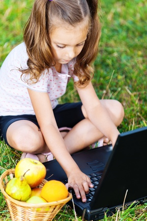 portrait of a beautiful, serious girl (child) sitting on the grass with laptop and basket of fruit (apples, pears, oranges) photo