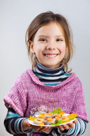 portrait of a beautiful, smiling little girl holding plate of food (herring rolls) on gray background