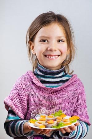 portret van een mooie, lachende meisje houdt bord eten (haring rollen) op een grijze achtergrond
