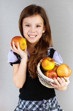 portrait of pretty, smiling, long-haired girl in dress holding wicker basket with apples on gray background