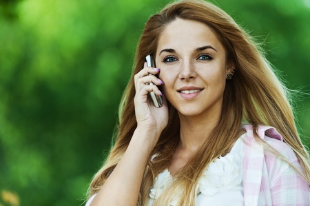 beautiful young woman with long hair, talking on the phone, smiling, background summer green park photo