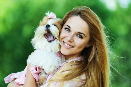mujer con perro: Retrato de la bella, joven, sonriente sosteniendo perro mullido pequeño, contra el fondo del verano parque verde