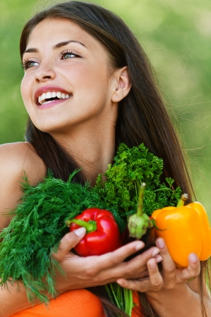 portrait of beautiful dark-haired smiling girl set with vegetables and herbs (eggplant, Bulgarian pepper red and yellow, dill and parsley) in hands on green background photo