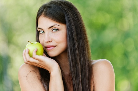 long-haired young woman with bare shoulders holding green apple background summer green park Stock Photo