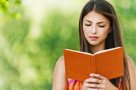 serious young, beautiful girl holding an open book, read background summer green park photo