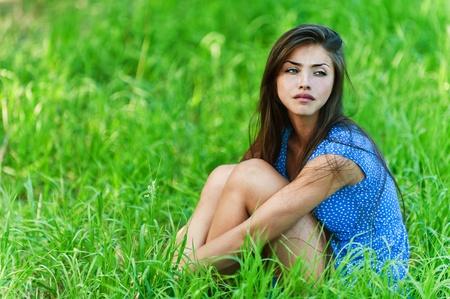 mujer sentada: verano fondo verde hierba joven encantadora, triste, de pelo largo en la mujer vestido azul sentada abrazándose las piernas